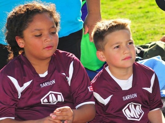 Derek Kulpa and his Mighty Minions teammate Mia Bellamy listen closely as their coach, Amy Gardea, goes over the game plan for the second half of their soccer game Saturday, April 16, at Provencio Van Dam soccer fields in Las Cruces.