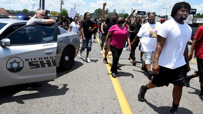 Marchers walk past a Richmond County Sheriff's officer as they march on Wrightsboro Road in protest of the killing of a black man by a white police officer in Minnesota recently.  Photographed in Augusta, Ga., Saturday afternoon May 30, 2020.