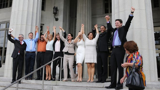 Same-sex couples in Miami celebrate Circuit Court Judge Sarah Zabel's lifting of the legal stay she had placed on her July decision declaring the wedding ban discriminatory, Monday, Jan. 5, 2015, in Miami. Miami-Dade County Clerk Harvey Ruvin says he will begin issuing licenses immediately, so the first gay and lesbian weddings could take place Monday afternoon.  (AP Photo/The Miami Herald, Emily Michot)  MAGS OUT