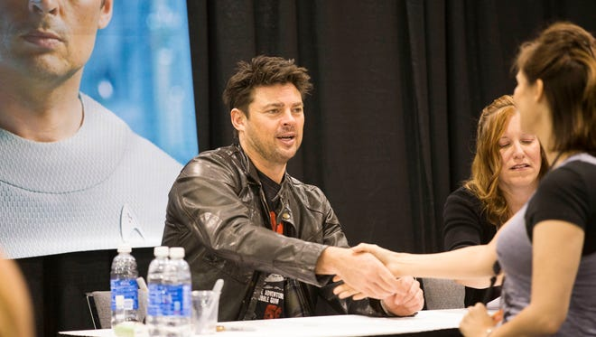 Actor Karl Urban shakes hands with a fan during the final day of Comicon at the Phoenix Convention Center May 31 2015.
