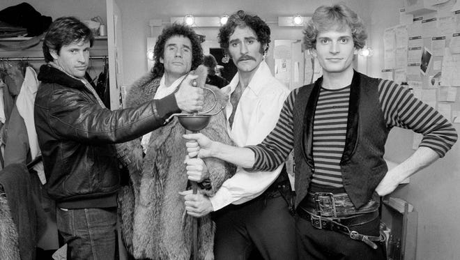 """Actors Robert Hays, left, and Jim Dale, second from left, have a try at the sword with Kevin Kline and Rex Smith, right, stars of the Broadway play """"The Pirates of Penzance,"""" after a performance in New York, Jan. 20, 1981."""
