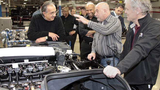 Fiat Chrysler CEO Sergio Marchionne, left, talks with plant worker Emidio Cardillo, center, during a visit to a Detroit factory in 2013