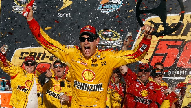 Joey Logano celebrates in the victory lane after winning the NASCAR Sprint Cup Series auto race Sunday at Phoenix International Raceway.