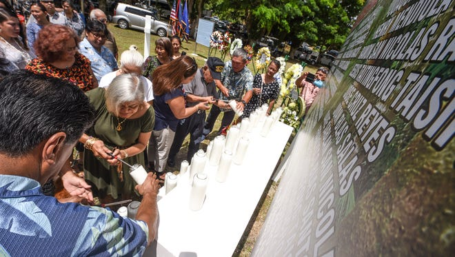 Descendants of Chagui'an massacre victims and others light candles and place them at the base of a sign bearing the names of the 45 men being remembered during a memorial service at the Chagui'an massacre site in Yigo on Tuesday, Aug. 8, 2017. During the recapture of the northern part of Guam by American soldiers from Japanese Imperial armed forces in World War II, U.S. Marines discovered a Japanese truck loaded with the bodies of decapitated Chamorro men. A further search of the area after the gruesome discovery, resulted in the finding 21 men, remaining in a kneeling position with their hands bound behind their backs and all beheaded.