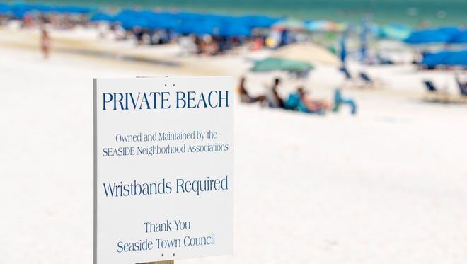"""A sign posted by the Seaside Neighborhood Associations and Seaside Town Council claims this stretch of sand as a """"Private Beach"""" in Walton County, Florida on Wednesday, July 19, 2017."""