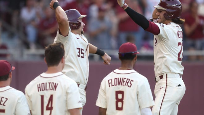 FSU's Cal Raleigh, left, greets Drew Mendoza at home plate to celebrate his 2-run home run against Miami during the Seminole's 10-1 win over the Hurricanes at Dick Howser Stadium on Saturday, April 28, 2018.