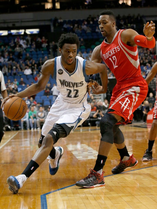 Minnesota Timberwolves guard Andrew Wiggins, left,  drives against Houston Rockets center Dwight Howard, right, during the first half of an NBA basketball game in Minneapolis, Monday, April 11, 2016. (AP Photo/Ann Heisenfelt)