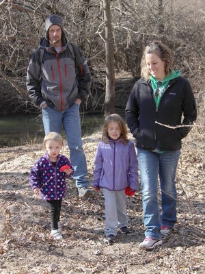 """The Lankard family enjoys a hike together on the Kansas Department of Wildlife, Parks and Tourism Green Recreation Trail on the """"First Day Hike."""" Many families took advantage of the mild weather to walk part of all of the trail. Family members are dad Kelsey, mom Kaci, Riley and Tayler."""