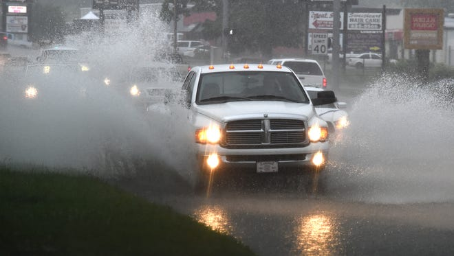 Vehicles travel through a flooded U.S. Highway 62 in Mountain Home on Tuesday, June 16, 2015. The Twin Lakes Area could see up to four inches of rain over the next few days.