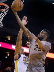 Phoenix Suns guard Reggie Bullock, right, lays up a
