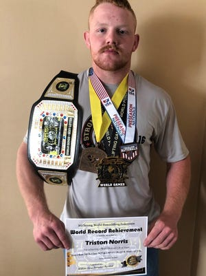 North Henderson High senior Triston Norris poses with his medals and awards he's won this year, including the World Powerlifting title and his third-place medal for the Preseason Nationals held last weekend.