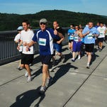The Walkway Over the Hudson has become a favorite place for area runners, and a favorite site for road races. Pictured, Kingston's John Nuss, center, leads a pack of runners during the annual Mid-Hudson Road Runners Club Rooftops to Treetops to Rooftops 5K.