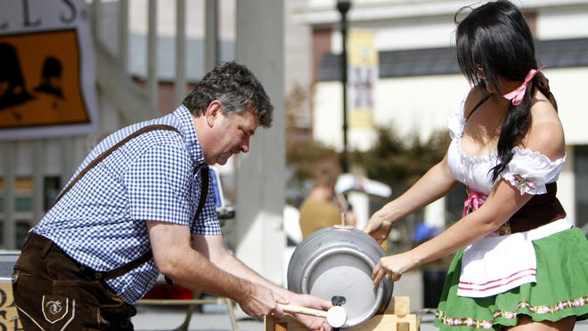Jeff Schrag taps the ceremonial first keg of Octoberfest Village during last year's Taste of Springfield on Park Central Square.