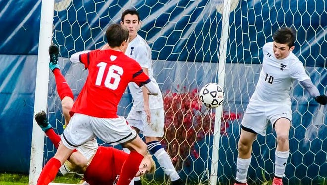Holden Dippel ,bottom left, of Mason kicks the ball past Ryan Lynch ,10, of Trenton for a goal early in the 2nd half of their Division 2 regional semifinal game Wednesday.