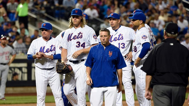 New York Mets manager Terry Collins, left, looks to the dugout as a trainer escorts starting pitcher Noah Syndergaard (34) from the mound in the fifth inning of a baseball game against the Washington Nationals, Friday, July 8, 2016, in New York.
