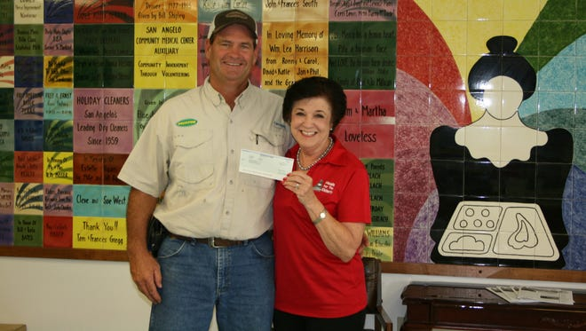 Meals For The Elderly President and CEO Charlyn Ocker accepted a check for $10,000 from Monsanto Fund representative Gregory Schwertner on July 20 at the Meals For The Elderly office.