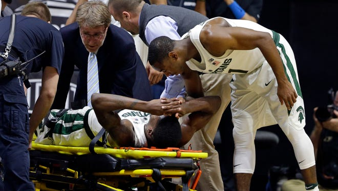 Michigan State guard Eron Harris gets some words of encouragement from Lourawls Nairn Jr. as he is wheeled off the court following a knee injury.
