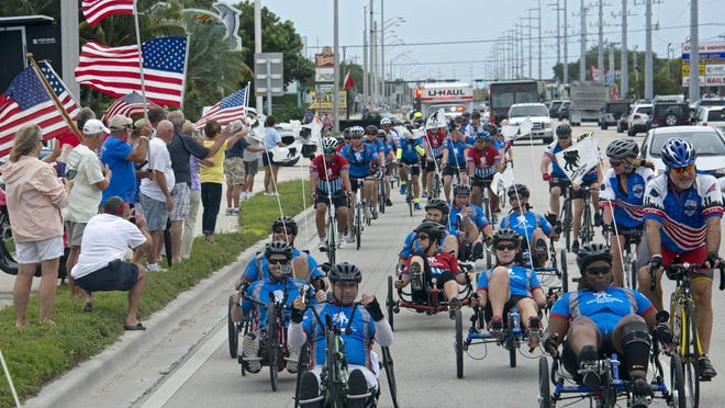 FILE- Flag-wavers greet wounded soldiers traversing the Florida Keys Overseas Highway in Marathon. Injured military personnel and supporters participated in Soldier Ride, staged by the Wounded Warrior Project to help restore injured soldiers' physical and emotional well-beings.