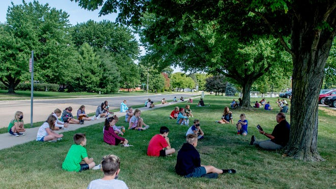 Fifth-graders sit outside in a socially-distanced grouping and listen to teacher Mike Finck read aloud during a literature class Tuesday at Lettie Brown Elementary School in Morton.