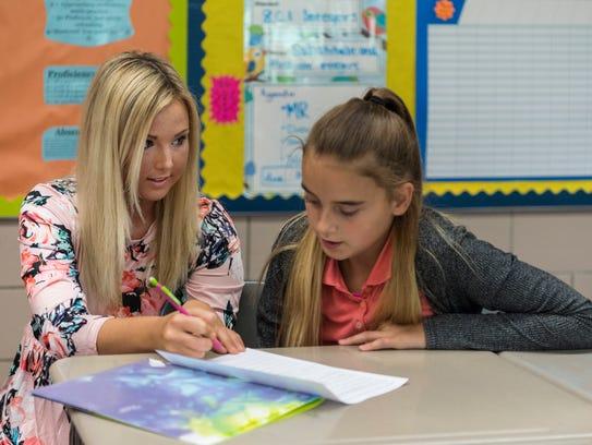 Math teacher Megan Beard helps seventh grader Brooklyn