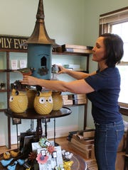 Barb Thomas organizes a display in her new gift shop,