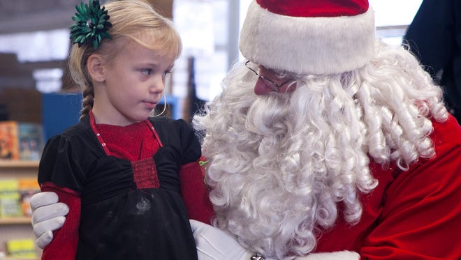 In this 2013 file photo, Santa Claus visits with a girl at North Elementary School in Cedar City.