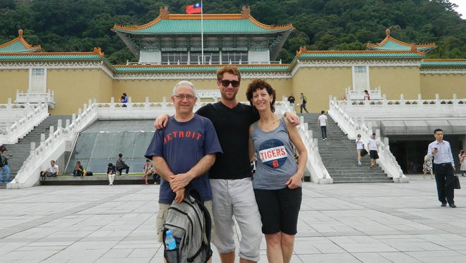 Partners Dan Schottenfels, left, and Sue Michlin and her son Dylan Michlin show off the Old English D at the National Palace Museum in Taipei, Taiwan. Dylan is an English teacher in Hsinchu, Taiwan. Sue and Dan live in Farmington Hills.