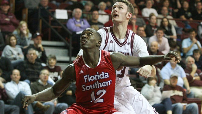 Florida Southern guard, Dominique Williams (12) blocks out Bellarmine forward, Josh Derksen (33) during the second half of play at Knight's Hall. December 13, 2014.
