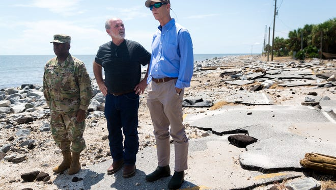 Gov. Rick Scott, right, surveys Hurricane Hermine damage with Florida National Guard Maj. Gen. Michael Calhoun, left, and Franklin County commissioner William Massey, center, in the Alligator Point community of Franklin County, Fla. on Sept. 3, 2016. Scott toured hurricane-damaged communities of the Big Bend area of Florida Saturday where the Category 1 storm hit landfall early Friday morning.