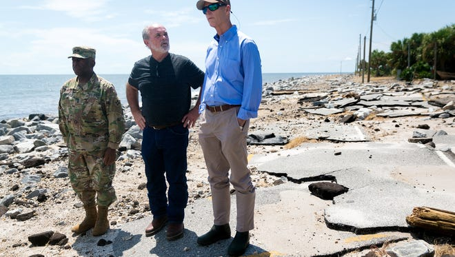 Florida Gov. Rick Scott, right, surveys Hurricane Hermine damage with Franklin County commissioner William Massey, center, and Florida National Guard Maj. Gen. Michael Calhoun, left, in Alligator Point on Sept. 3, 2016. Over the years, the rural beach community in the Florida Panhandle has lost sections of road, sea walls and two dozen homes to beach erosion.