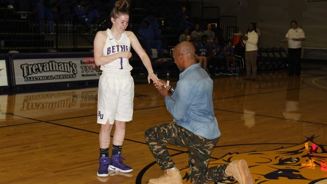 Bethel University basketball player and Madison Academic graduate Cayla Sheets reacts as Jensen Youngblood puts an engagement ring on her finger before the Lady Wildcats' game on Thursday at Bethel.