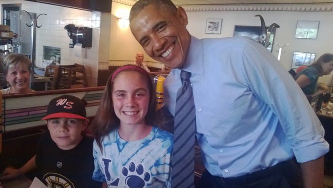 Kyla Campell, 13, and her brother Brody, 8, had their picture taken with President Barack Obama during a visit to the Charcoal Pit on Concord Pike Thursday. Pat Grim, of Newark, can be seen in the background.