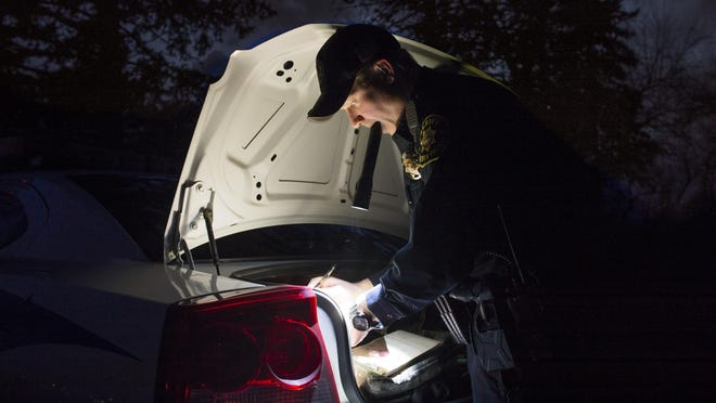 Martin Swanty, a deputy with the Larimer County Sheriff's Office, gathers paperwork in the back of his cruiser as he responds to a domestic violence call in Fort Collins on Feb. 18. Swanty is in charge of patrolling an area east of city limits including the East Mulberry Street corridor.