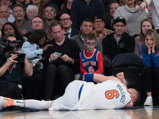 New York Knicks forward Kristaps Porzingis lies on the ground after being injured during the first half of the team's NBA basketball game against the Milwaukee Bucks, Tuesday, Feb. 6, 2018, at Madison Square Garden in New York. (AP Photo/Mary Altaffer)