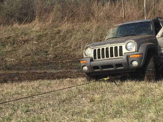 Two truck operator winches  19-year-old's Jeep Liberty onto his truck.