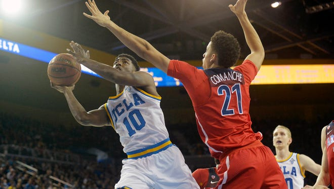 UCLA Bruins guard Isaac Hamilton drives on Arizona Wildcats center Chance Comanche.