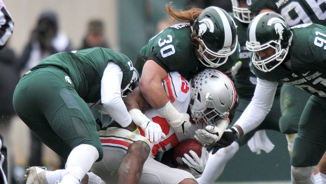 The Michigan State defense stops Buckeye Mike Weber (25) on the line of scrimmage for no gain.