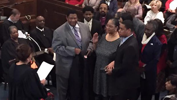 LaRita Cooper-Stokes goes hatless as she is sworn in as judge Monday.