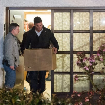 Police carry computer, a box and bags out of the residence
