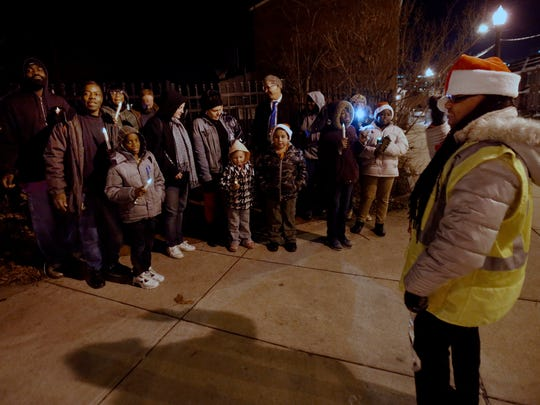 Carolers led by Pastor Sandra Ben sing holiday songs at the corner of E. 22nd and Lamotte streets before hitting other locations in the city Wednesday in memory of S.U.N. (Safe United Neighborhoods) member Melvin Smith, who was killed in a stabbing incident in center city.