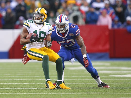 Packers receiver Randall Cobb (18) spins away from the tackle by Bills Nigel Bradham (53).