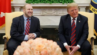 President Donald Trump, right, and Joshua Holt, who was recently released from a prison in Venezuela, smile in the Oval Office of the White House, Saturday, May 26, 2018, in Washington.