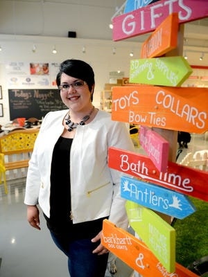 Melissa Allen stands at the entrance to Kids N Dogs, near the tinkrLab area inside Kids N Dogs, July 5, 2016 with her bassett hound Stewie. The human portion of Kids N Dogs has expanded into a mini makerspace for kids called tinkrLAB. Store owner Allen's special project has been to expose girls to STEM programming, get them excited about the possibilities, and empower them to invent, build and make.