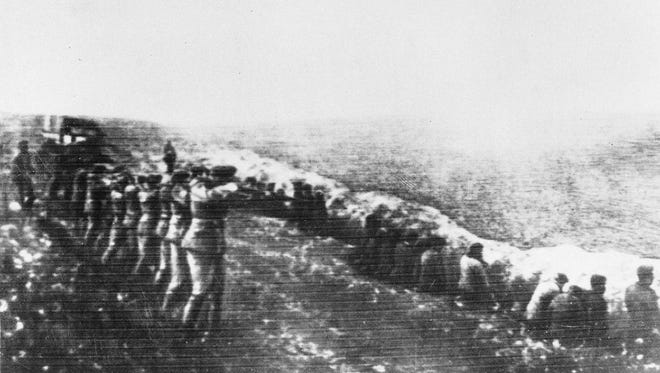 This 1942 file photo shows a Nazi firing squad shooting Soviet civilians in the back as they sit beside their own mass grave, in Babi Yar, Kiev.