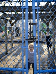 A youngster near the new blue gate at Tennyson Park in Passaic, which was installed to keep children from wandering outside the playground.