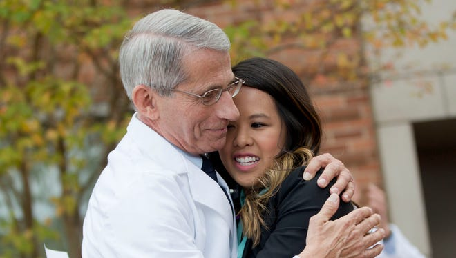 Patient Nina Pham is hugged by Dr. Anthony Fauci, director of the National Institute of Allergy and Infectious Diseases, outside of National Institutes of Health in Bethesda, Md., on Oct. 24, 2014. Pham, the first nurse diagnosed with Ebola after treating an infected man at a Dallas hospital is free of the virus.