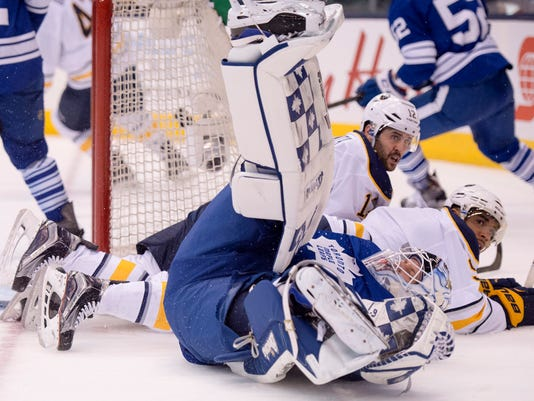 Toronto Maple Leafs' goalie Garret Sparks is leveled by Buffalo Sabres' Brian Gionta and Evander Kane during first period NHL in Toronto on Monday, March 7, 2016. Kane got a goaltender interference penalty on the play. (Frank Gunn/The Canadian Press via AP)