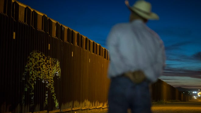 An image of a jaguar is projected on the border wall on May 12, 2017, in Douglas, Ariz.