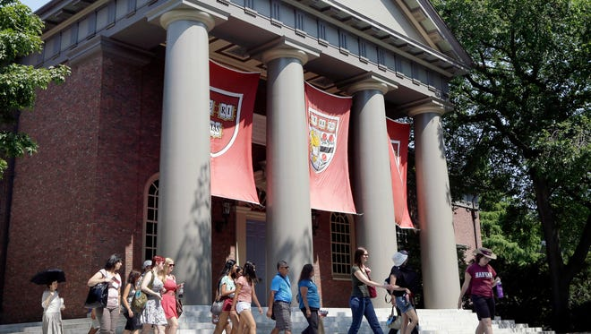 In this Aug. 30, 2012, file photo, a tour group walks through the campus of Harvard University in Cambridge, Mass.