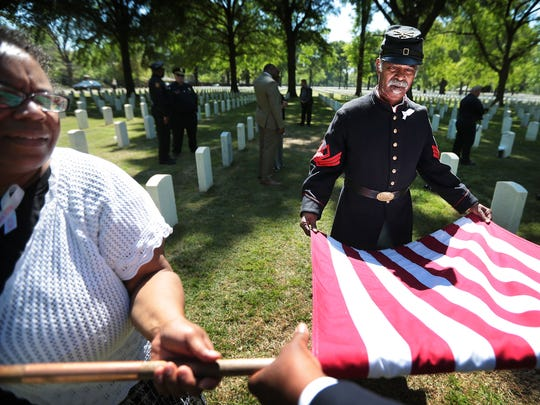 Yulanda Burgess (left) and Civil War reenactor Robert Bell, 67, roll up an American flag from the Civil War era after a ceremony at the Memphis National Cemetery to honor the African American Union troops slaughtered by Confederates on April 12, 1864 after the garrison at Fort Pillow surrendered. The graves of over 100 of the victims were recently found at the local veterans cemetery.